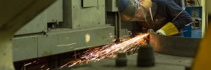 Worker fabricating metal with angle grinder