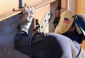 Workers' hands grasp tubing in tube shop