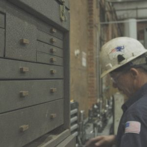 Worker looks through drawers, brandishing American flag and Patriots logo.