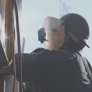 Man welding with american flag decal on helmet