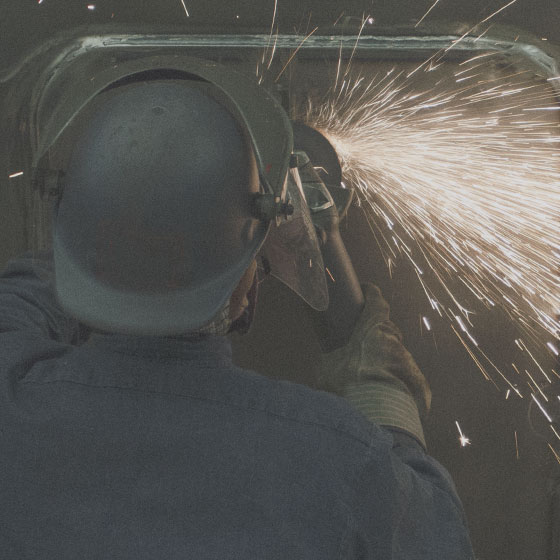 A worker uses machinery in the shop.
