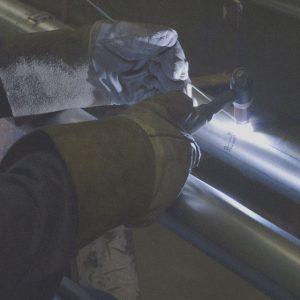 Workers' gloved-hands tighten metal parts.