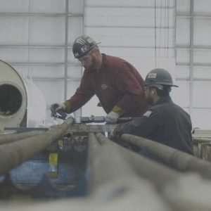 Two employees work on machinery.