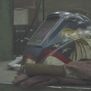 Digital welders helmet sits at MIG welding workstation