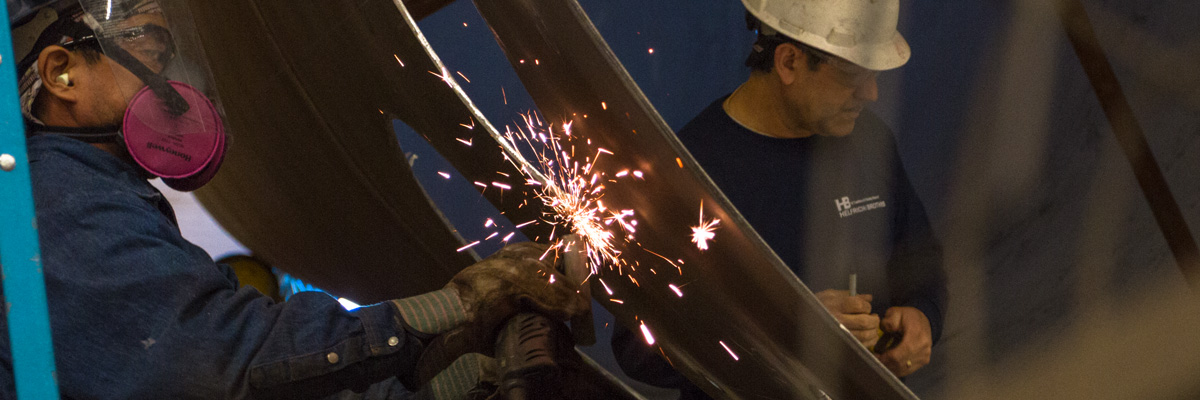 Worker fabricates metal with angle grinder