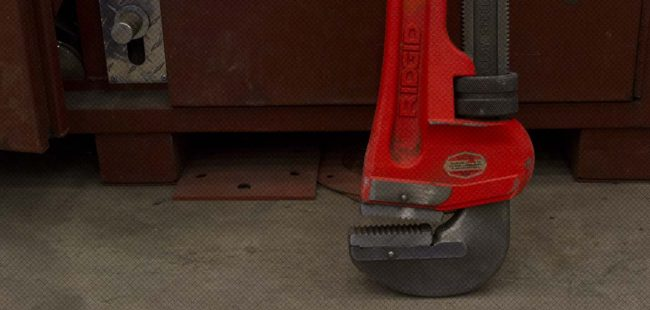 Close up of large adjustable wrench on shop floor