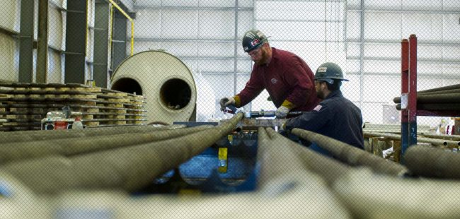 Two workers adjust bent tubing